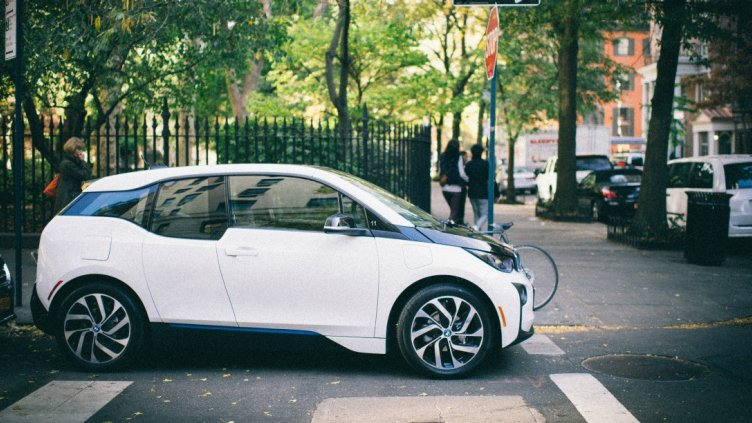 white electric car at stop sign